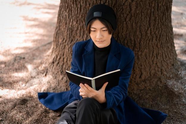 Mężczyzna czyta w parku przed drzewem