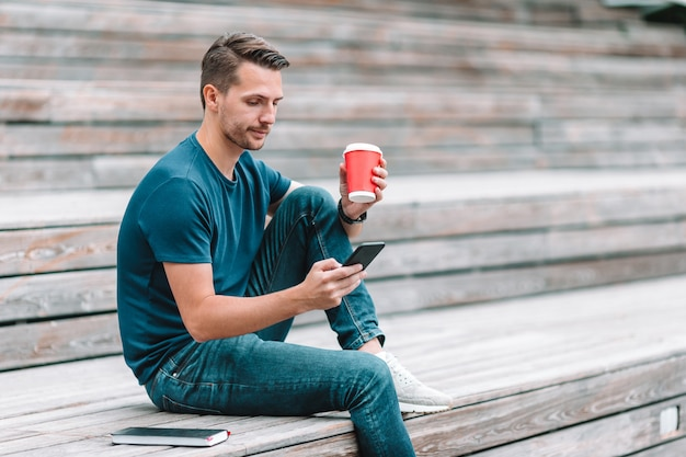 Mężczyzna czyta wiadomość tekstową na telefonie komórkowym podczas gdy chodzący w parku
