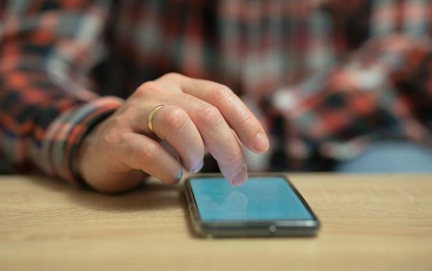 Mężczyzna czyta wiadomości na swoim telefonie komórkowym, który leży na drewnianym stole. zbliżenie na złoty pierścionek na prawym palcu mężczyzny