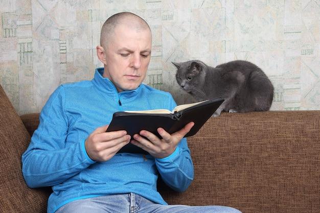 Mężczyzna czytając książkę relaksując się na kanapie z kotem