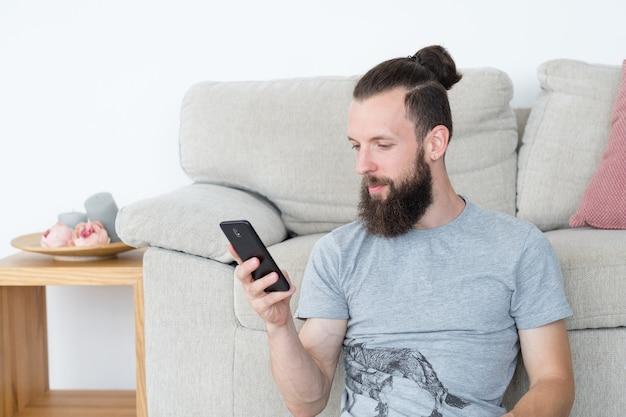 Mężczyzna czytając telefon komórkowy blogując bezczynny styl życia