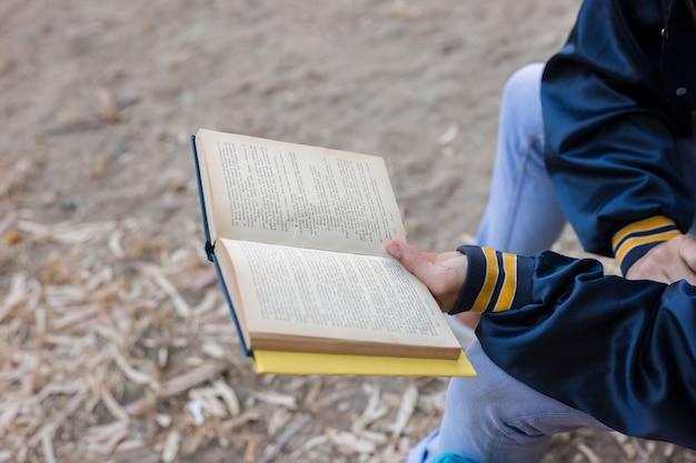 Mężczyzna czytająca książkę na zewnątrz