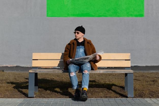 Mężczyzna czytający gazetę siedzący na ławce w słoneczny dzień