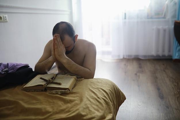 Mężczyzna czytający i modlący się z pisma świętego przy łóżku wieczorem. chrześcijanie i koncepcja studium biblii. studiowanie słowa bożego w kościele.