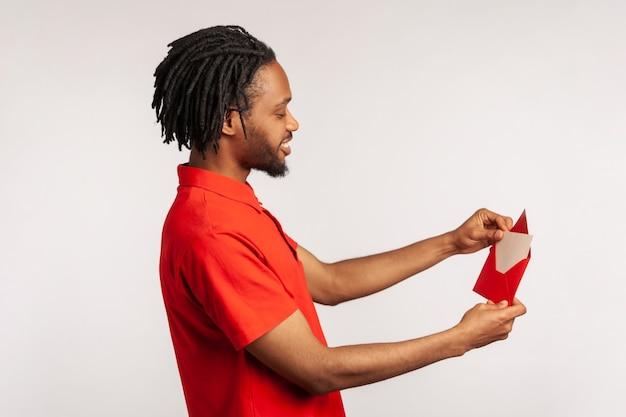 Mężczyzna czytający list lub kartkę z życzeniami, trzymając kopertę, uśmiechając się i ciesząc się przyjemną wiadomością.
