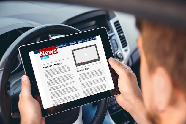 Mężczyzna czytający wiadomości z tabletem w ręku za kierownicą samochodu