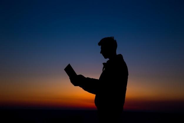 Mężczyzna czytanie w polu przeciw zmierzchowi