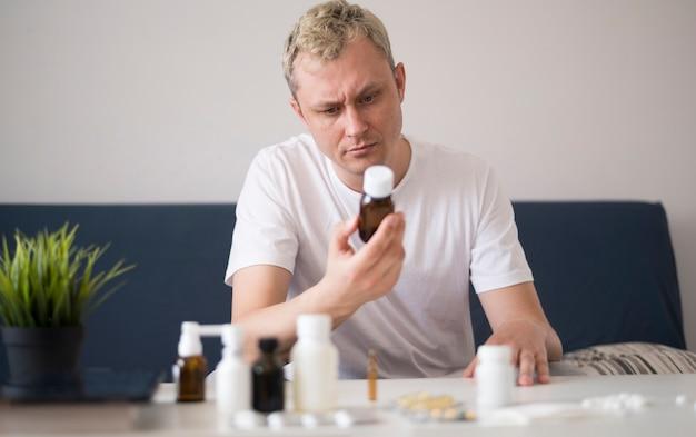 Mężczyzna czytanie ze szklanego pojemnika leczenia