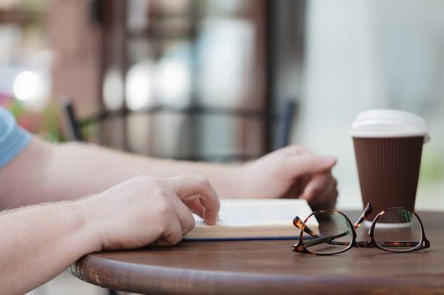 Mężczyzna czytelnicza książka z kawą lub herbatą