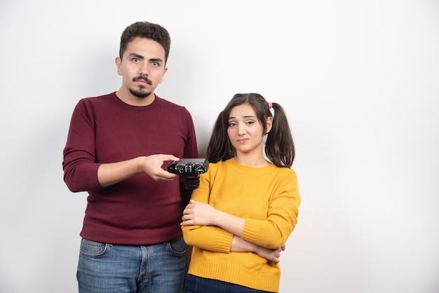 Mężczyzna daje aparat młodej kobiecie na białej ścianie.