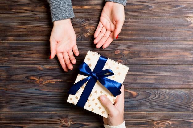 Mężczyzna daje boże narodzenie pudełko w ręce kobiety