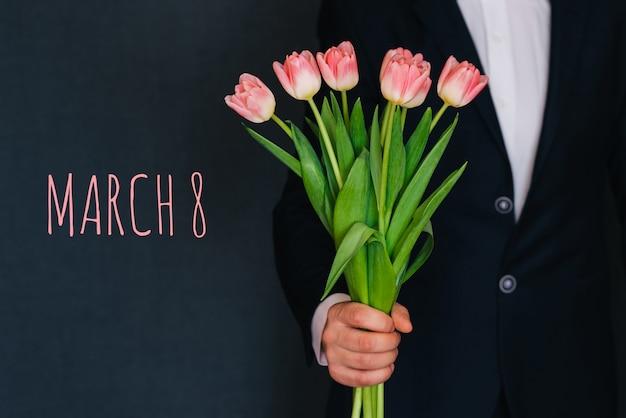 Mężczyzna daje bukietowi różowych kwiatów tulipany. kartkę z życzeniami z tekstem 8 marca