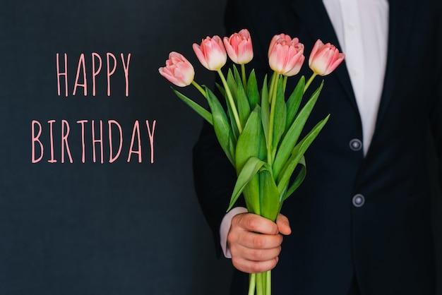 Mężczyzna daje bukietowi różowych kwiatów tulipany. kartkę z życzeniami z tekstem wszystkiego najlepszego