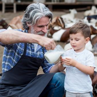 Mężczyzna daje chłopcu mleko kozie