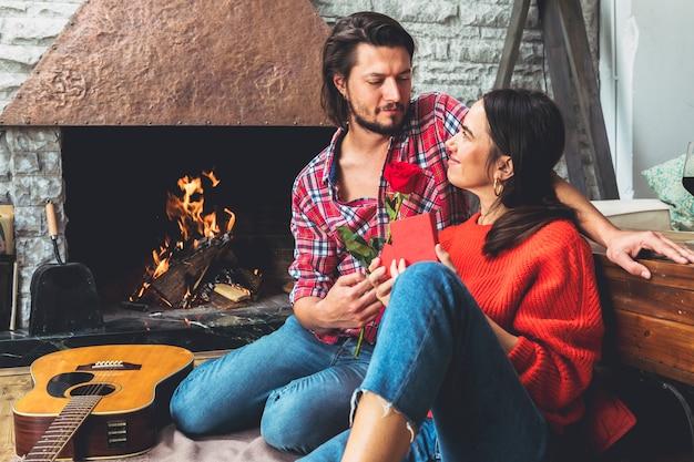 Mężczyzna daje czerwieni róży kobieta na podłoga