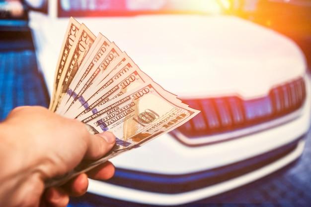 Mężczyzna daje dolara jako zapłatę za zakup lub naprawę samochodu. koncepcja zakupu nowego, nowoczesnego samochodu
