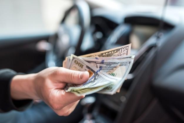 Mężczyzna daje dolary siedząc w samochodzie. koncepcja zakupów, pieniądze