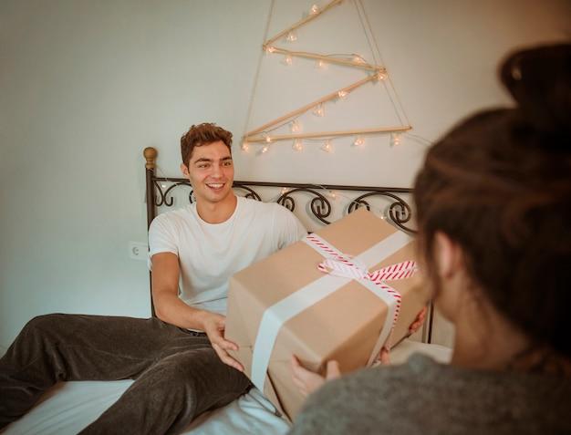 Mężczyzna daje dużemu prezentowi pudełko kobieta