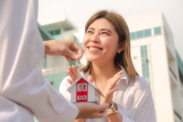 Mężczyzna daje klucz domu kobietom szczęśliwa rodzina koncepcja para kocham rodzinną firmę sprzedaż ubezpieczenia inwestycji