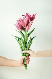 Mężczyzna daje kobiecie kwiaty. męski i żeński ręki mienia bukiet na białym tle