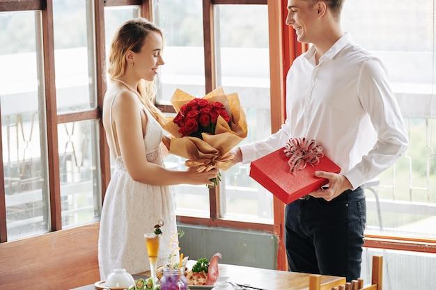 Mężczyzna daje kwiaty dziewczynie