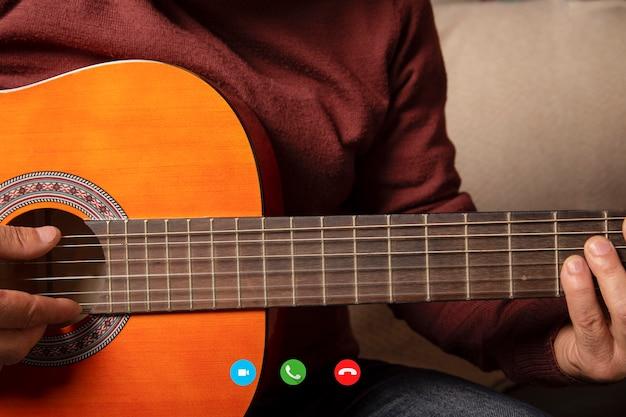 Mężczyzna daje lekcje gry na gitarze akustycznej podczas rozmowy wideo.