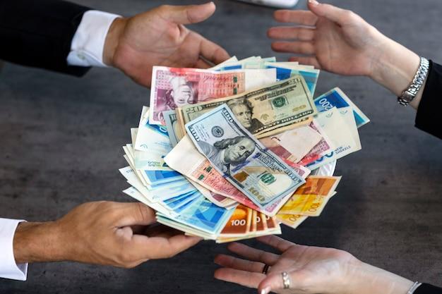 Mężczyzna daje pieniądze kobiecie w talerzu z amerykańskimi i izraelskimi pieniędzmi, zbliżenie rąk. biznesmen biorąc łapówkę od kobiety. pojęcie korupcji, finanse, rachunkowość. bizneswoman z tacą (talerz) gotówką