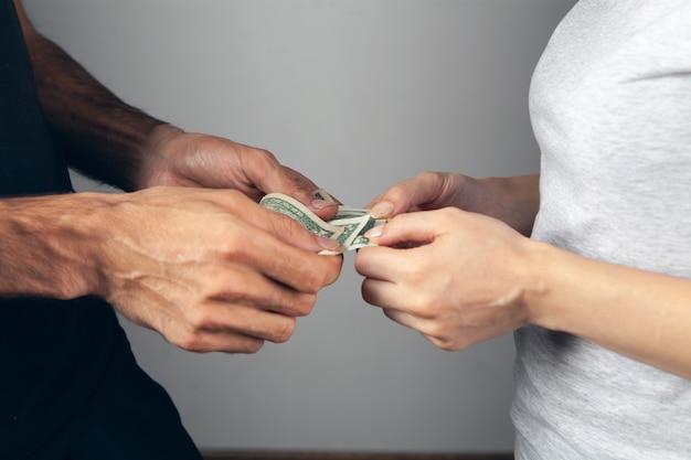 Mężczyzna daje pieniądze kobiecie