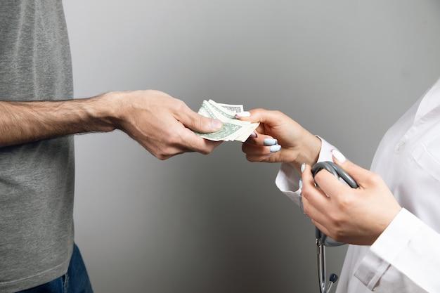 Mężczyzna daje pieniądze lekarzowi na szarym tle