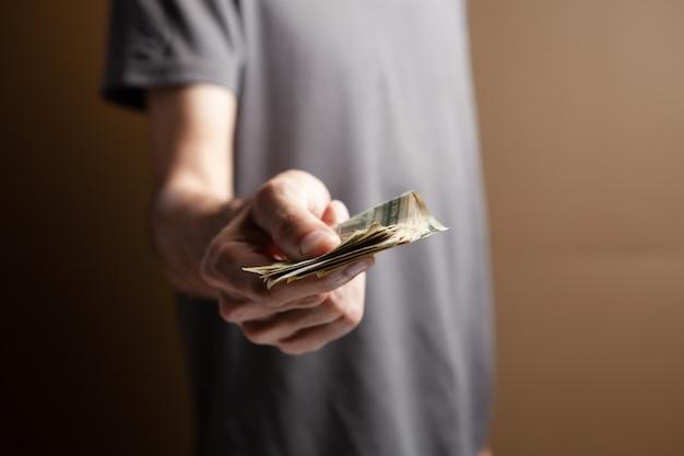 Mężczyzna daje pieniądze na brązowym tle
