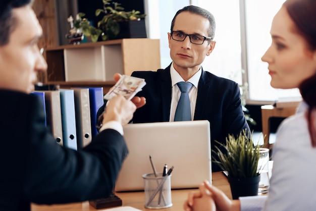 Mężczyzna daje pieniądze prawnikowi za rozwód, siedząc w biurze.
