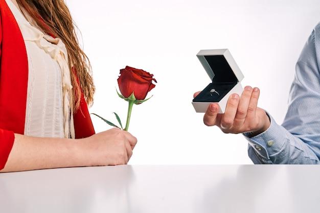 Mężczyzna daje pierścionek zaręczynowy swojemu partnerowi i czerwoną różę. koncepcja walentynki, para zakochanych i propozycja małżeństwa.