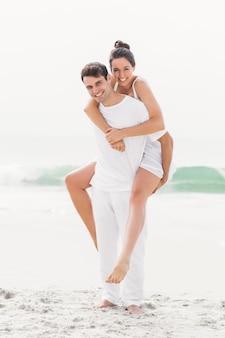 Mężczyzna daje piggyback kobiecie na plaży