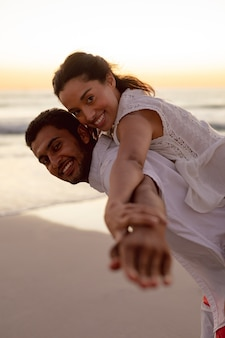 Mężczyzna daje piggyback przejażdżce kobieta na plaży