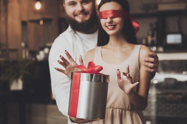 Mężczyzna daje prezent dziewczynie z zamkniętymi oczami