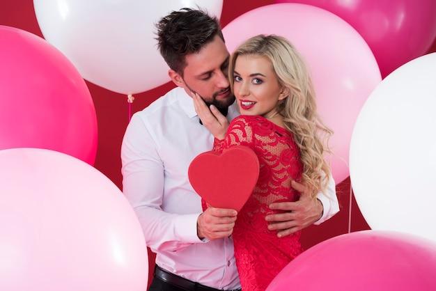 Mężczyzna daje swojej ukochanej kobiecie pudełko w kształcie serca