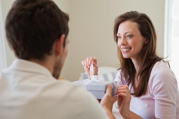 Mężczyzna daje szczęśliwej kobiecie prezenta pudełko