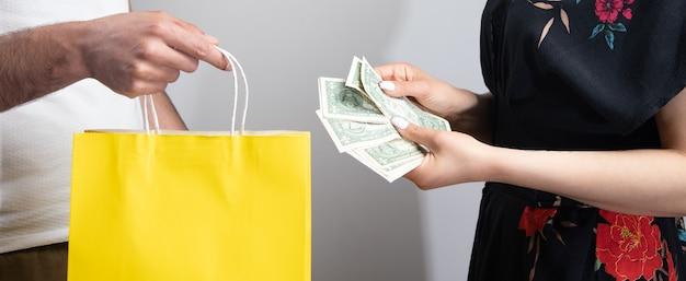 Mężczyzna daje worek na prezent, a kobieta za to płaci