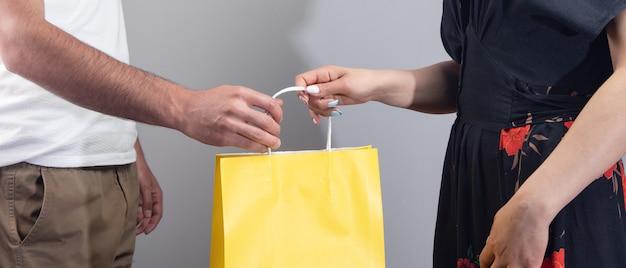 Mężczyzna daje worek na prezent kobiecie na szarym tle