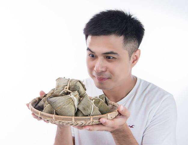 Mężczyzna daje zongzi lub kluskę ryżową innym jako prezent lub pamiątka na festiwalu smoczych łodzi, azjatyckie tradycyjne jedzenie, białe tło