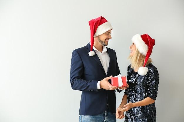 Mężczyzna daje żonie świąteczny prezent na jasnym tle