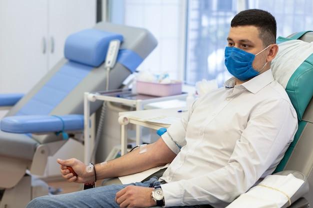 Mężczyzna dawca w masce medycznej od koronawirusa oddającego krew w laboratorium. zapobieganie covid-19 w transfuzji hemodializy