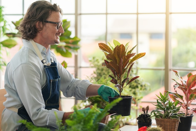Mężczyzna dbający o jej rośliny doniczkowe w domu, ogrodnictwo, sadzenie w domu