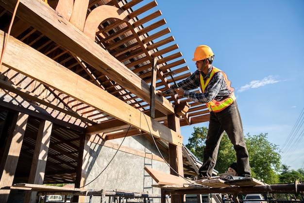 Mężczyzna-dekarz, cieśla pracujący na konstrukcji dachu na budowie