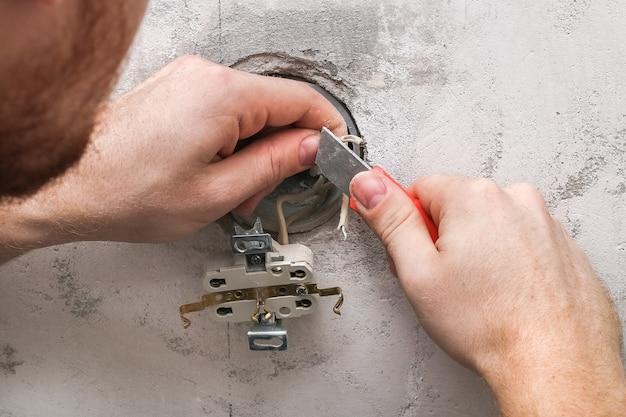 Mężczyzna demontuje i naprawia gniazdko elektryczne w celu naprawy gniazdka