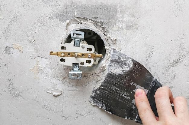 Mężczyzna demontuje i naprawia gniazdko elektryczne w celu naprawy. gniazdo zasilania.