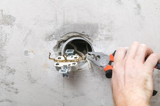 Mężczyzna demontuje i naprawia gniazdko elektryczne w celu naprawy