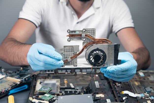 Mężczyzna demontuje laptopa na szarej ścianie
