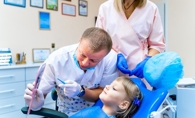 Mężczyzna dentysta trzymając lustro przed pacjentką dziewczynki