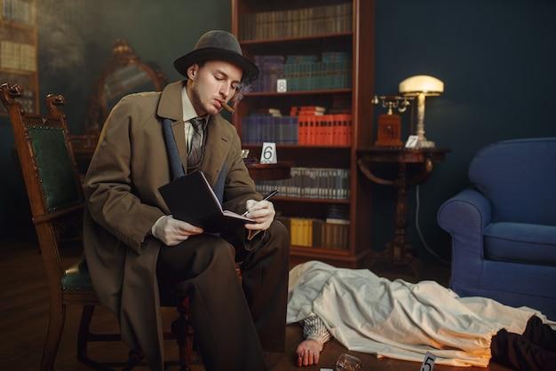Mężczyzna detektyw z cygarem pisze w zeszycie, ofiara pod peleryną na miejscu zbrodni